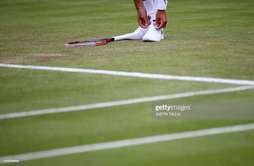 Australia's Bernard Tomic ties his shoelaces as he plays Spain's Fernando Verdasco in a men's singles first round match on the third day of the 2016 Wimbledon Championships at The All England Lawn Tennis Club in Wimbledon, southwest London, on June 29, 2016. / AFP / JUSTIN