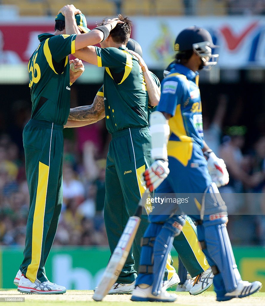 Australia's bowler Mitchell Starc (L) celebrates with teammate Mitchell Johnson (C) after taking the wicket of Angelo Mathews (R) of Sri Lanka during their one-day international cricket match at the Gabba in Brisbane on January 18, 2013.  AFP PHOTO / Bradley KANARIS USE