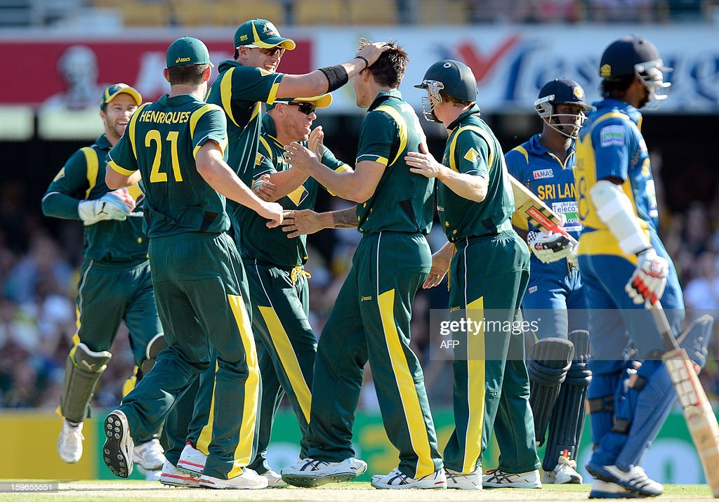 Australia's bowler Mitchell Starc (3rd L) celebrates with teammate Mitchell Johnson (5th L) after taking the wicket of Angelo Mathews (far R) of Sri Lanka during their one-day international cricket match at the Gabba in Brisbane on January 18, 2013. AFP PHOTO / Bradley KANARIS USE