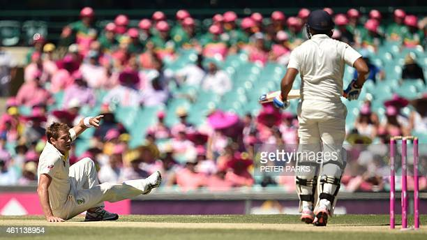 Australia's bowler Ryan Harris falls after going for the rebound as India's batsman Karn Sharma looks on during day three of the fourth cricket Test...