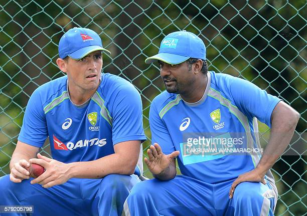 Australia's bowling consultant Sri Lankan former cricketer Muttiah Muralitharan speaks with Australian cricketer Stephen O'Keefe during a practice...
