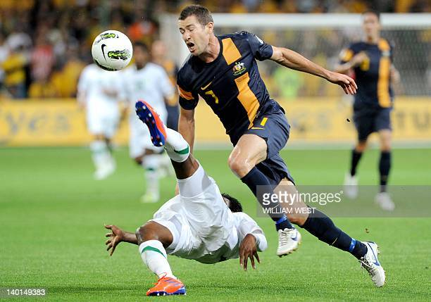 Australia's Brett Emerton is tackled by Saudi Arabia's Kamil Saddiq Almousa during their 2014 World Cup qualifying match in Melbourne on February...