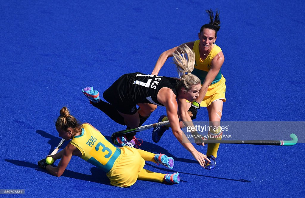 TOPSHOT Australia's Brooke Peris and Australia's Madonna Blyth vie with New Zealand's Sophie Cocks during the the women's quarterfinal field hockey...