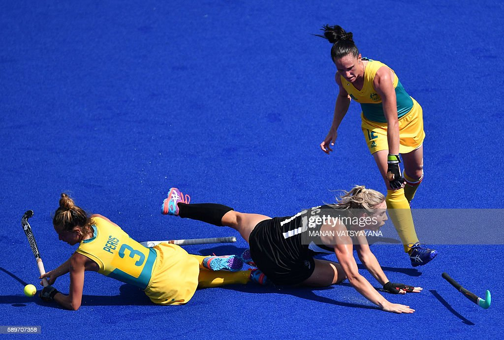 Australia's Brooke Peris and Australia's Madonna Blyth vie with New Zealand's Sophie Cocks during the the women's quarterfinal field hockey New...