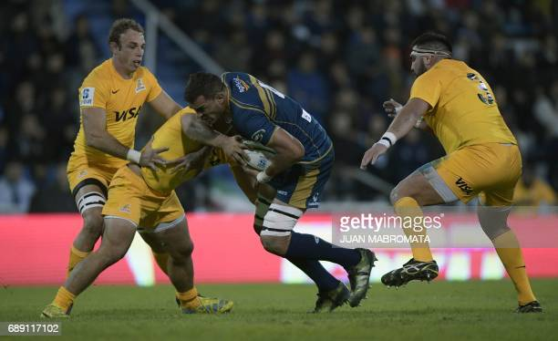 Australia's Brumbies lock Rory Arnold is tackled by Argentina's Jaguares hooker Agustin Creevy N8 Leonardo Senatore next to teammate Argentina's...