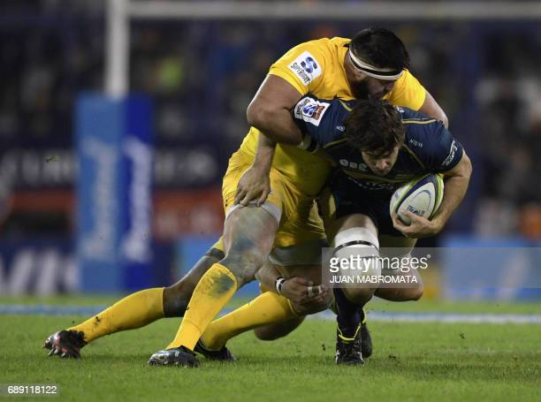 Australia's Brumbies lock Sam Carter is tackled by Argentina's Jaguares prop Ramiro Herrera and prop Lucas Noguera Paz during their Super Rugby match...