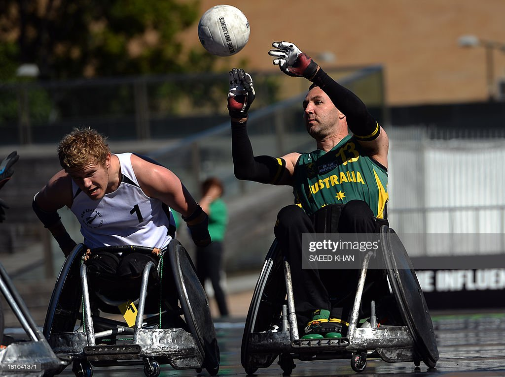 Australia's Cameron Carr (R) passes a ball to his teammate as New Zealand's Cameron Leslie (L) defends during their Wheelchair Rugby Tri-Nations match in front of St. Mary's Cathedral in Sydney on September 19, 2013. Wheelchair Rugby, which is also know as mederball due to its aggressive, full-contact nature, originated in Canada in 1977 and combines the elements of basketball, football and ice hockey. AFP PHOTO / Saeed KHAN USE