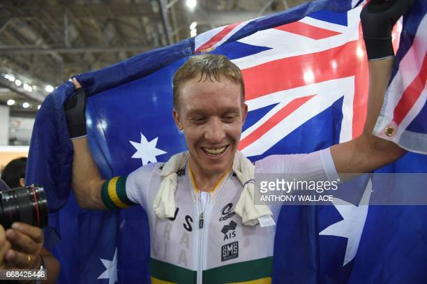 Australia's Cameron Meyer holds his national flag after winning the men's points race final at the Hong Kong Velodrome during the Track Cycling World...