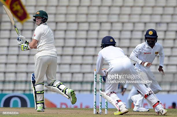 Australia's captain Steven Smith watches as Sri Lanka's wicketkeeper Dinesh Chandimal breaks the stumps to dismiss Smith during the second day of...