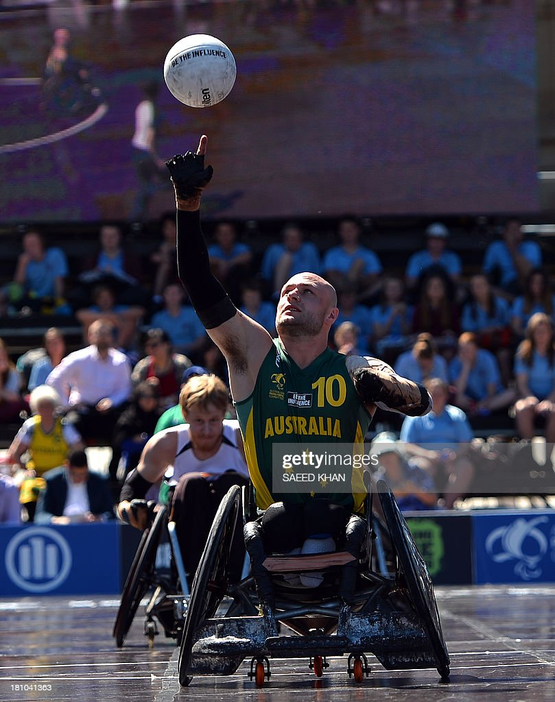 Australia's Chris Bond (C) grabs a ball during their Wheelchair Rugby Tri-Nations match against New Zealand in front of St. Mary's Cathedral in Sydney on September 19, 2013. Wheelchair Rugby, which is also know as mederball due to its aggressive, full-contact nature, originated in Canada in 1977 and combines the elements of basketball, football and ice hockey. AFP PHOTO / Saeed KHAN USE
