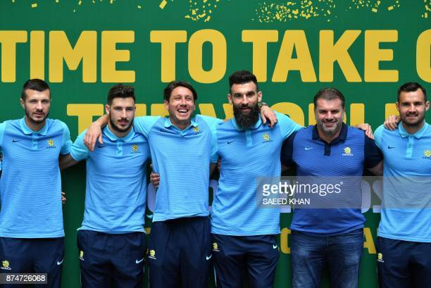 Australia's coach Ange Postecoglou and captain Mile Jedinak pose for photographs with teammates during an event to celebrate the national teams...