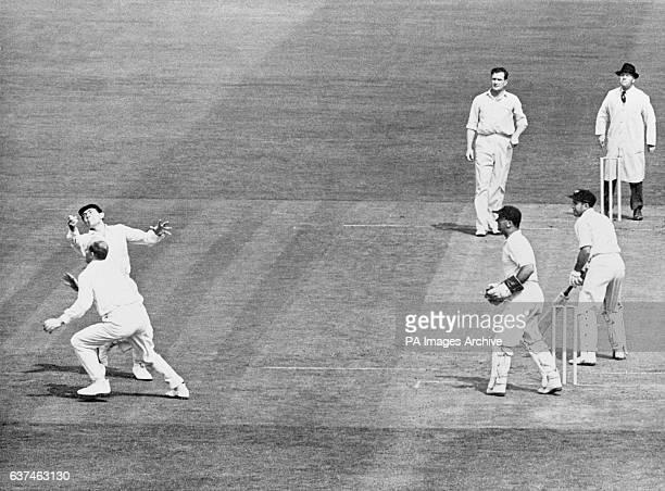 Australia's Colin McDonald turns a ball from England's Jim Laker over the head of Tony Lock as wicketkeeper Godfrey Evans looks on