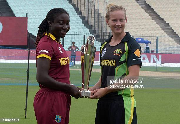 Australia's cricket women's team captain Meg Lanning and the West Indies captain Stefanie Taylor hold the World T20 tournament trophy at the Eden...