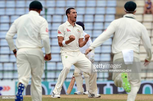 Australia's cricketer Mitchell Starc celebrates with teammates after he dismissed Sri Lanka's cricketer Kusal Perera during the second day of the...