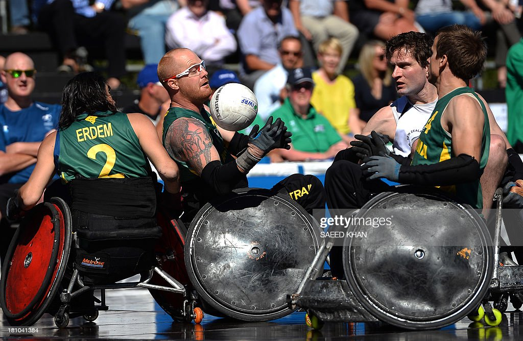 Australia's Curtis Palmer (C) tries to grab the ball during their Wheelchair Rugby Tri-Nations match against New Zealand in front of St. Mary's Cathedral in Sydney on September 19, 2013. Wheelchair Rugby, which is also know as mederball due to its aggressive, full-contact nature, originated in Canada in 1977 and combines the elements of basketball, football and ice hockey. AFP PHOTO / Saeed KHAN USE