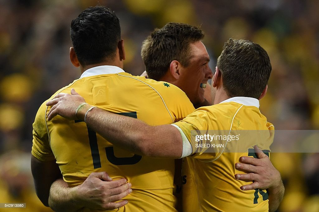 Australia's Dane Haylett-Petty (C) celebrates a successful try against England with teammates during their third and final rugby union Test match in Sydney on June 25, 2016. / AFP / SAEED