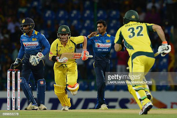 Australia's David Warner and Glenn Maxwell run between the wickets as Sri Lanka's wicketkeeper Kusal Perera and Dhananjaya de Silva look on during...