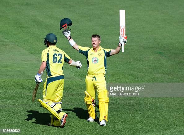 Australia's David Warner celebrates a century with Travis Head during the third match of the one day international cricket series between Australia...