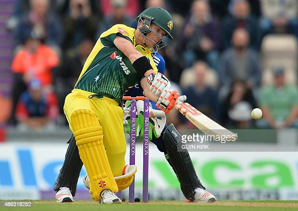 Australia's David Warner hits the ball before losing his wicket for 59 runs to a catch from England's Chris Woakes off the bowling of England's Adil...