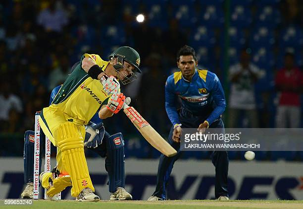 Australia's David Warner is watched by Sri Lanka's Dhananjaya de Silva as he plays a shot during the first T20 international cricket match between...