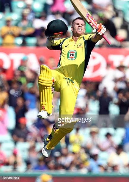 Australia's David Warner leaps into the air as he celebrates after scoring a century during the fourth oneday international cricket match between...