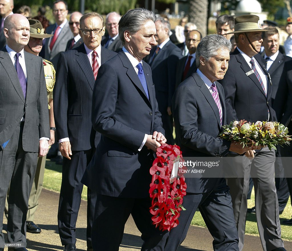 Australia's Defence Minister Stephen Smith (R) and Britain's Defence Secretary Philip Hammond (C) lay wreaths at Perth's Kings Park War Memorial, watched by Britain's Foreign Secretary William Hague (far L) and Australia's Foreign Minister Bob Carr (2nd L) before the commencement of the Australia-UK Ministerial Consultations (AUKMIN) in Perth on January 18, 2013. The event is an annual day-long summit between British ministers and their Australian counterparts. AFP PHOTO / Tony ASHBY