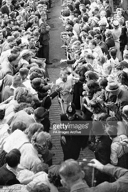 Australia's Don Bradman makes his way back to the pavilion through crowds of wellwishers after helping his team to victory with an unbeaten 173 on...