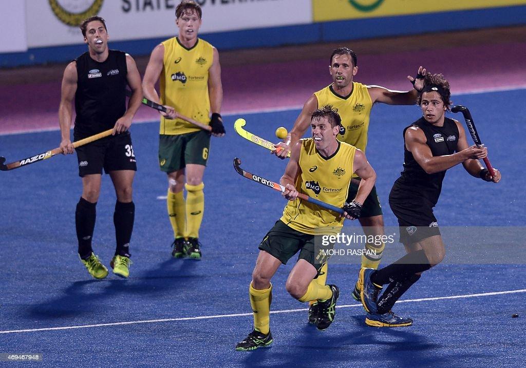 Australia's Eddie Ockenden eyes the ball against George Muir of New Zealand during the Sultan Azlan Shah Cup men's field hockey tournament finals in...