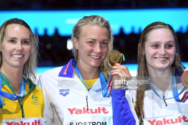 Australia's Emma Mckeon Sweden's Sarah Sjostrom and US Kelsi Worrell celebrate on the podium after the women's 100m butterfly final during the...