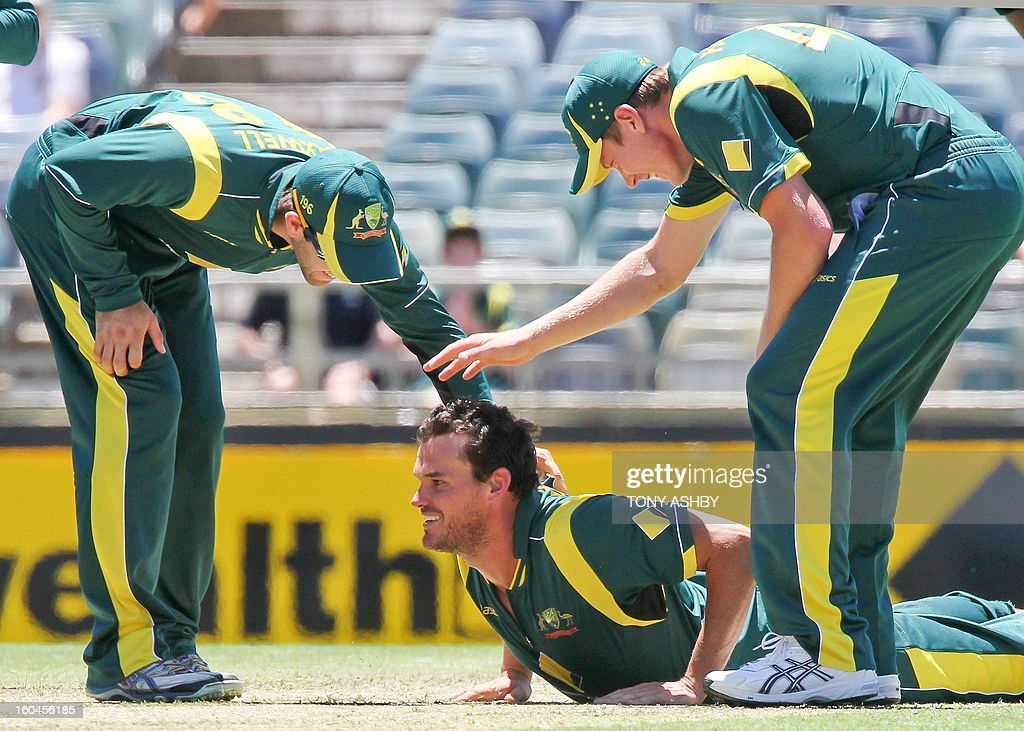 Australia's fast bowler Clint McKay (C) is congratulated by teamates Glenn Maxwell (L) and James Faulkner (R) after taking the wicket of West Indies batsman Darren Sammy (unseen) during the one-day international cricket match between Australia and the West Indies at the WACA ground on February 1, 2013. AFP PHOTO/Tony ASHBY USE