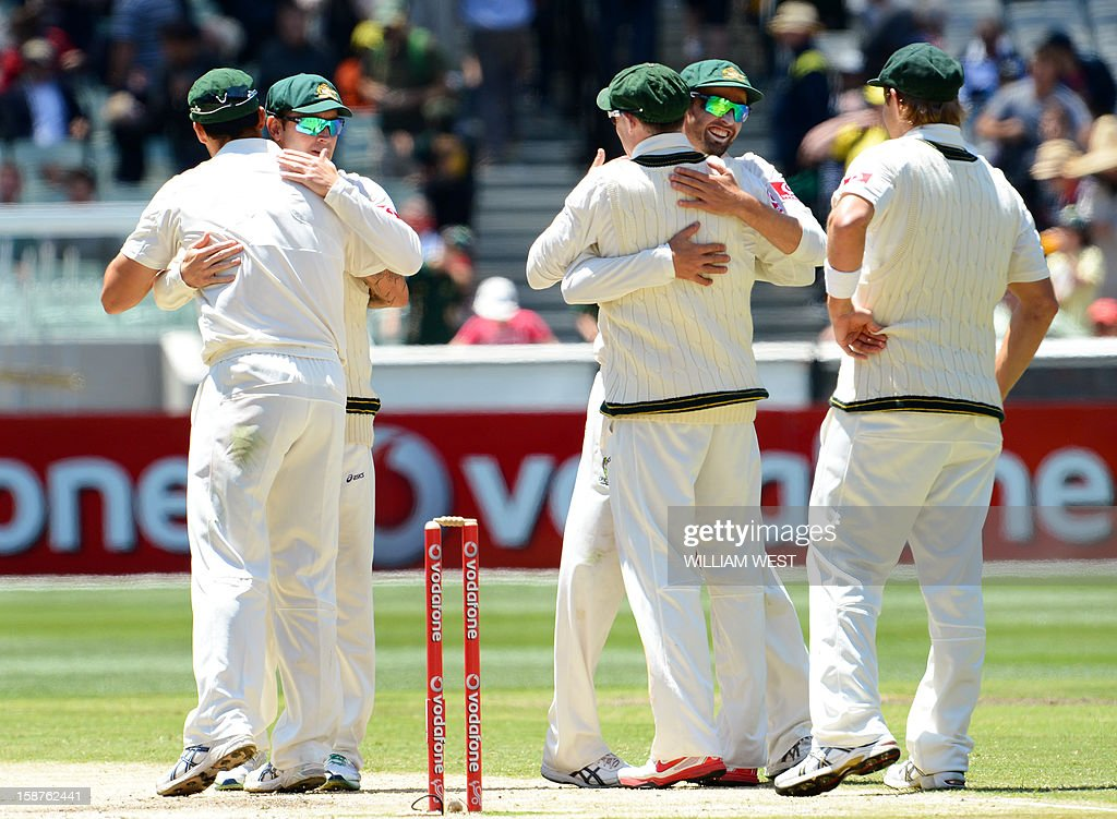 Australia's fast bowler Mitchell Johnson (L) is congratulated by captain Michael Clarke (2nd L) after Australia defeated Sri Lanka on the third day of the second cricket Test match at the Melbourne Cricket Ground (MCG) on December 28, 2012. AFP PHOTO/William WEST USE