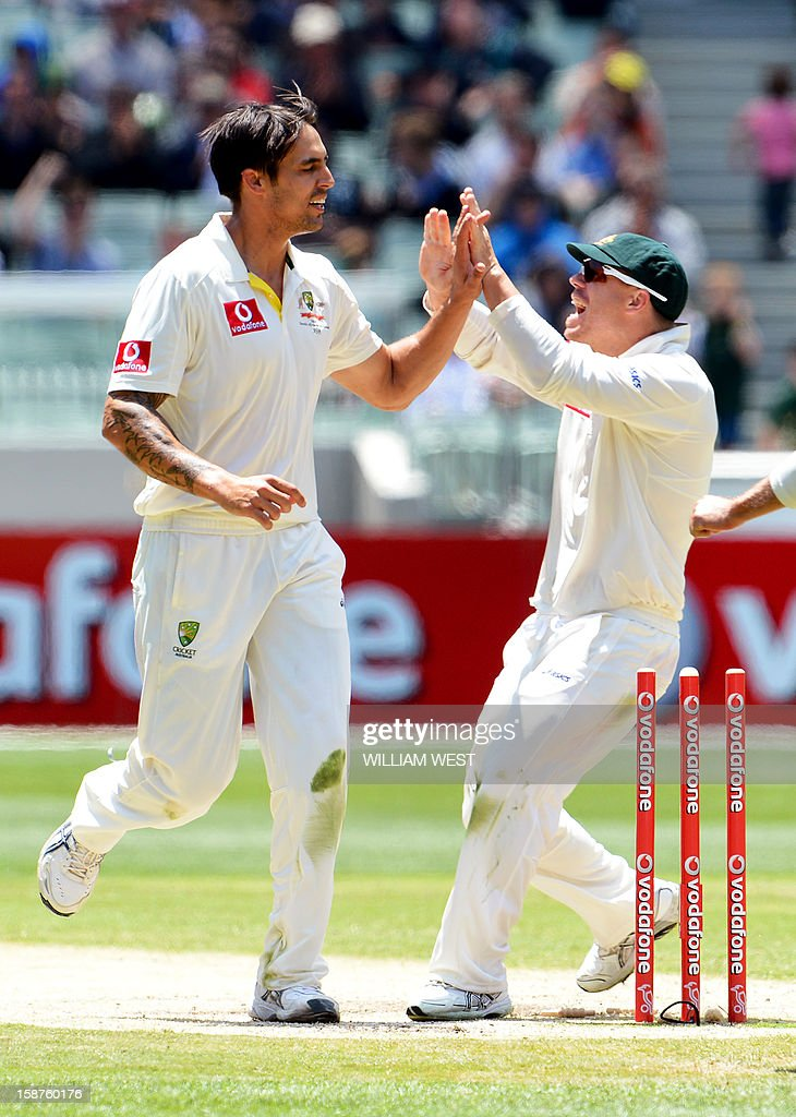 Australia's fast bowler Mitchell Johnson (L) is congratulated by teammate David Warner (R) after dismissing Sri Lanka's batsman Angelo Mathews on the third day of the second cricket Test match at the Melbourne Cricket Ground (MCG) on December 28, 2012. AFP PHOTO/William WEST USE