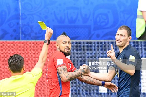 Australia's forward James Troisi receives a yello car while shaking hands with Chile's midfielder Arturo Vidal during the 2017 Confederations Cup...
