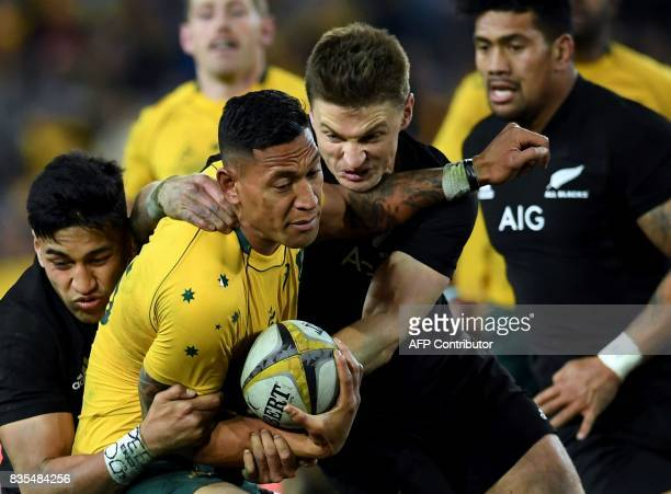 Australia's fullback Israel Folau is tackled by New Zealand's Beauden Barrett and Curtis Rona during the Rugby Championship test match between...