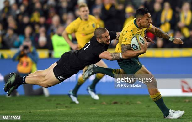 Australia's fullback Israel Folau scores a try as he is tackled by New Zealand's substitute TJ Perenara during the Rugby Championship test match...