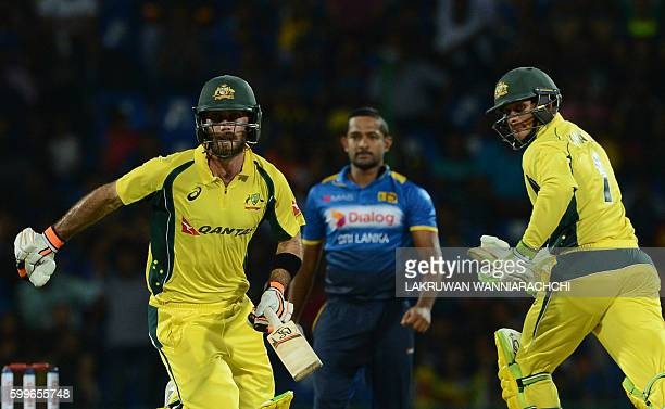 Australia's Glenn Maxwell and Usman Khawaja is watched by Sri Lanka's Sachith Pathirana as they run between the wickets during the first T20...