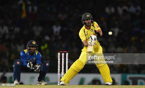 Australia's Glenn Maxwell hits a shot as Sri Lankan's Kusal Perera looks on during the final T20 international cricket match between Sri Lanka and...