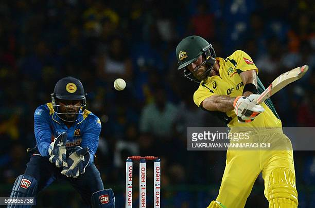 Australia's Glenn Maxwell is watched by Sri Lanka's wicketkeeper Kusal Perera as he hits a ball to the boundary during the first T20 international...