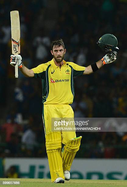 Australia's Glenn Maxwell raises his bat and helmet in celebration after scoring a century during the first T20 international cricket match between...