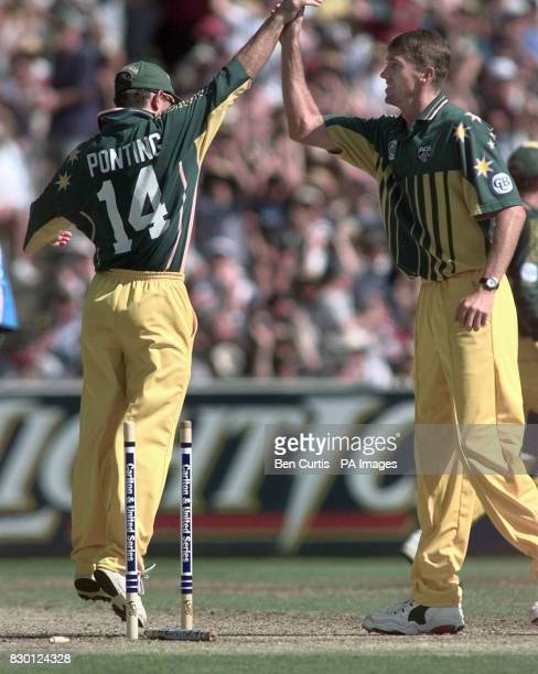 Australia's Glenn McGrath celebrates with teammate Ricky Ponting after McGrath ran out England's Robert Croft for two runs during their One Day...