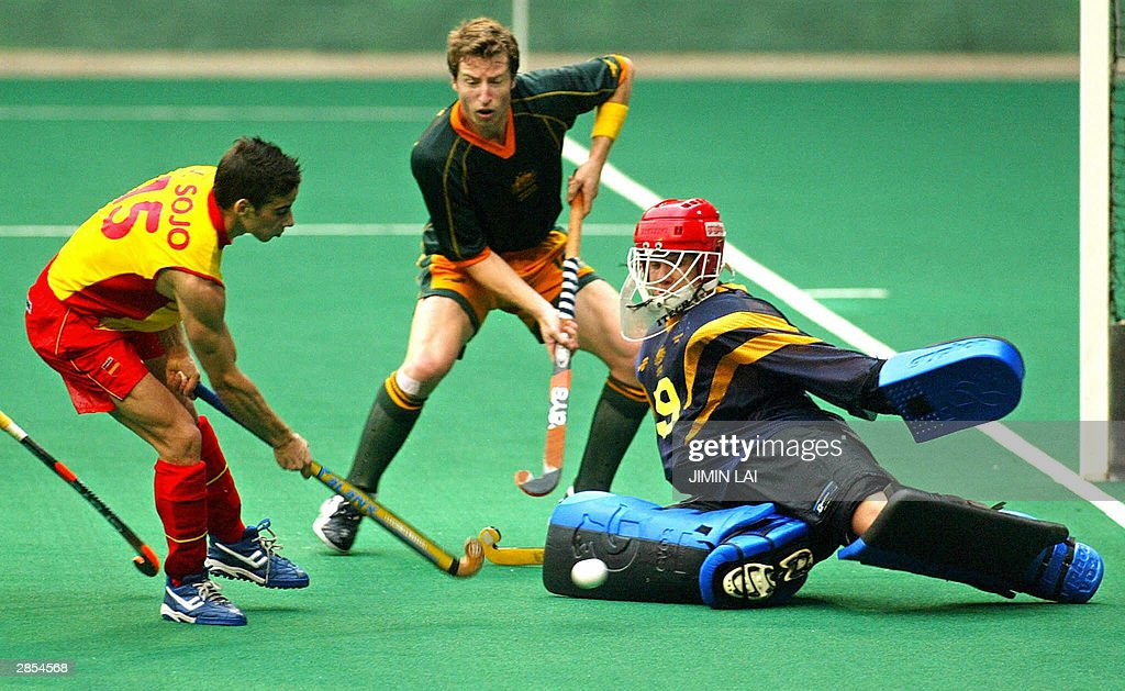 Australia's goalkeeper Mark Hickman saves the ball from a shot by Victor Sojo Gimenez of Spain while Josh Hawes of Australia looks on during the 13th...