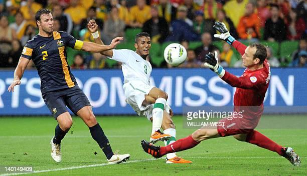 Australia's goalkeeper Mark Schwarzer blocks a shot by Saudi Arabia's Yahia Sulaiman Alshehri as Lucas Neill looks on during their 2014 World Cup...