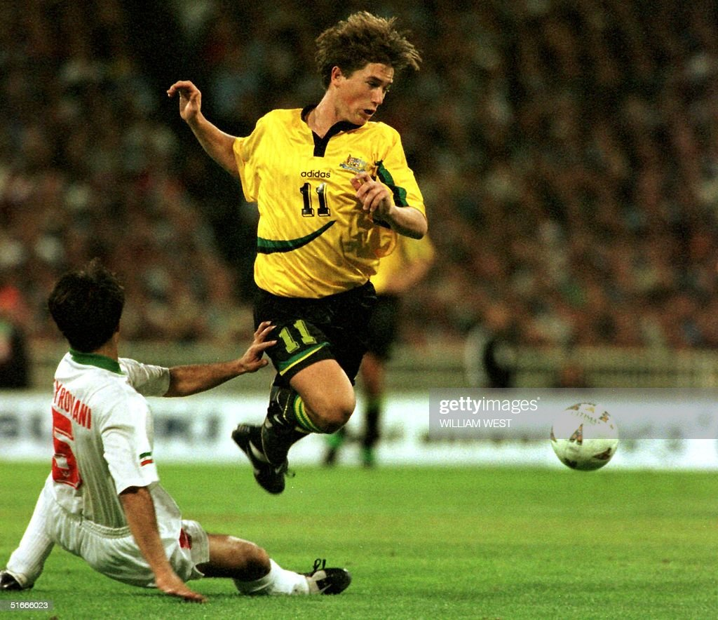 Australia's Harry Kewell is up ended by Iranian defender Mohammadali Pieravany as Australia attacks after Iran had scored two late goals to draw 2-2 and qualify for the 1998 World Cup finals at the Melbourne Cricket Ground in Melbourne 29 November. A crowd of 85,000 saw the underdogs Iran clinched the tie after being down 0-2 and progress to the final on the away goals ruling after drawing the first leg in Tehran 1-1.