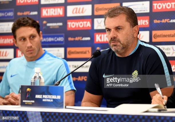 Australia's head coach Ange Postecoglou answers questions beside player Mark Milligan during a press conference at Saitama Stadium in Saitama on...