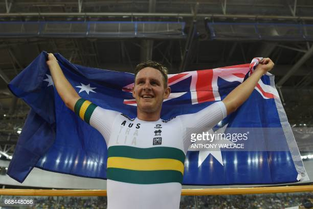 Australia's Jordan Kerby holds his national flag after winning the men's individual pursuit final at the Hong Kong Velodrome during the Track Cycling...