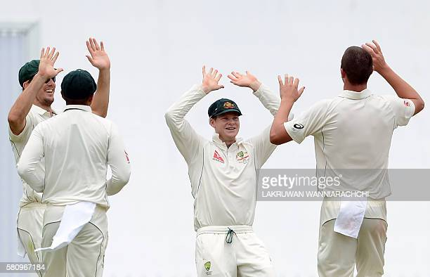 Australia's Josh Hazlewood celebrates with teammates including captain Steve Smith after he dismissed Sri Lanka's Dinesh Chandimal during the first...