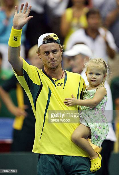 Australia's Lleyton Hewitt holds his daughter Mia as he waves to spectators after his win over Thailand's Kirati Siributwong in the Davis Cup...