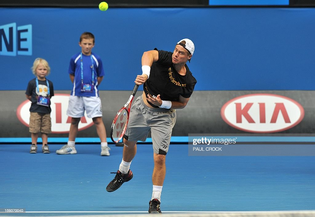 Australia's Lleyton Hewitt serves as his son Cruz and an unidentified child watch on during a training session ahead of the Australian Open tennis tournament in Melbourne on January 13, 2013. AFP PHOTO / PAUL CROCK IMAGE STRICTLY RESTRICTED TO EDITORIAL USE - STRICTLY NO COMMERCIAL USE