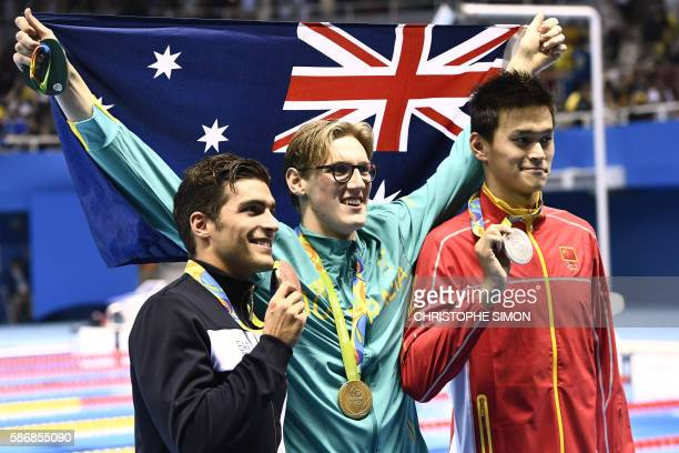Australia's Mack Horton holds the Australian flag as he poses on the podium with silver medallist China's Sun Yang and bronze medallist Italy's...