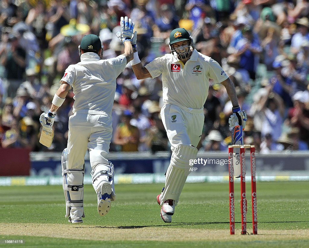 Australia's Michael Clarke (L) celebrates his 100 with teammate Mike Hussey (R) against South Africa on the first day of the second cricket Test match at the Adelaide Oval on November 22, 2012. AFP PHOTO/David Mariuz IMAGE STRICTLY FOR EDITORIAL USE - STRICTLY NO COMMERCIAL USE
